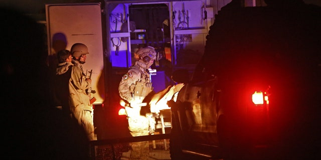 November 29, 2014: Afghan security personnel carry a dead body into an ambulance at the site of a battle between security forces and Taliban fighters in Kabul. (AP Photo/Massoud Hossaini)