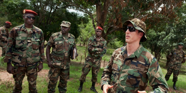 April 29, 2012: U.S. Army special forces Captain Gregory, 29, from Texas, right, who would only give his first name in accordance with special forces security guidelines, speaks with troops from the Central African Republic and Uganda, in Obo, Central African Republic.