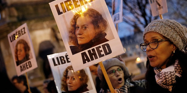 """In this Jan. 4, 2018 file photo, demonstrators hold posters reading, """"Release Ahed"""" during a protest demanding Israel to release Ahed Tamimi. Tamimi is to go on trial Tuesday, Feb. 13, 2018, before an Israeli military court, for slapping and punching two Israeli soldiers in December. Palestinians say her actions embody their David vs. Goliath struggle against a brutal military occupation, while Israel portrays them as a staged provocation meant to embarrass its military. Tamimi is one of an estimated 350 Palestinian minors in Israeli jails."""