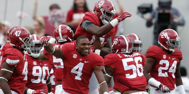 Oct 18, 2014; Tuscaloosa, AL, USA; Alabama Crimson Tide linebacker Reggie Ragland (19) is congratulated by teammates after he intercepted a pass from Texas A&M Aggies quarterback Kenny Hill (not shown) at Bryant-Denny Stadium. The Crimson Tide defeated the Aggies 59-0. Mandatory Credit: Marvin Gentry-USA TODAY Sports