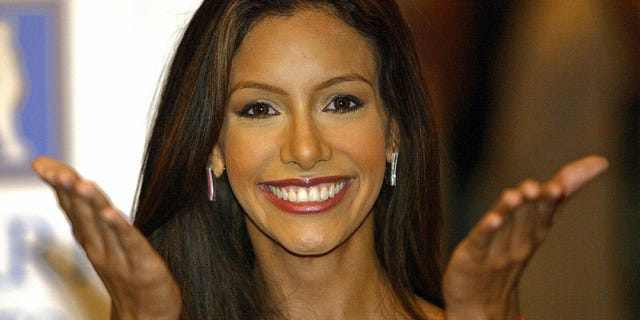 Miss Puerto Rico Alba Reyes waves to photographers on 31 May 2004, in Quito, Ecuador.