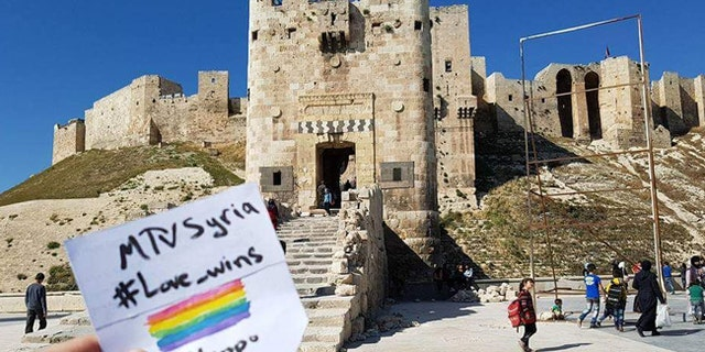 A supporter of MTV Syria - Love Wins is seen at the Citadel of Aleppo, a large medieval fortified palace in the center of the old city of Aleppo, northern Syria.