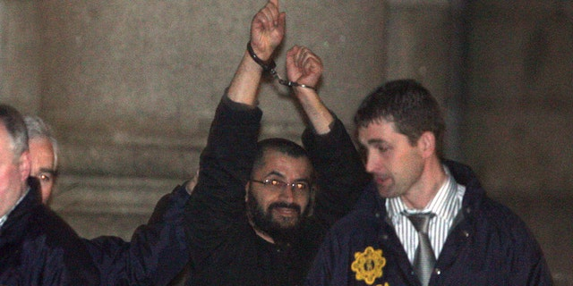 "Ali Charaf Damache, also known by the alias ""Black Flag,"" is accompanied by Irish law enforcement officials as he appears at Waterford District Court to be remanded into custody after being arrested on terrorism charges in Waterford, Ireland in this March 13, 2010 file photo."