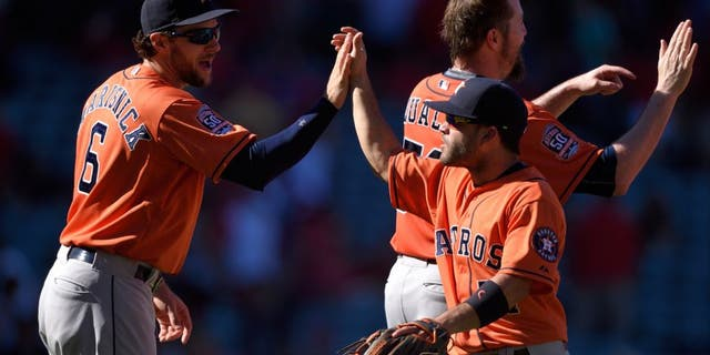 ANAHEIM, CA - SEPTEMBER 13: Jake Marisnick #6 and Jose Altuve #27 of the Houston Astros high-five while celebrating after defeating the Los Angeles Angels of Anaheim 5-3 at Angel Stadium of Anaheim on September 13, 2015 in Anaheim, California. (Photo by Matt Brown/Angels Baseball LP/Getty Images)