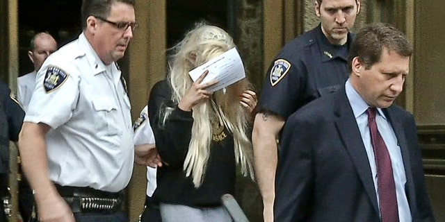 May 24, 2013: In an image made from video, actress Amanda Bynes, center, wearing sweats and a blonde wig, shields her face as she is escorted after a Manhattan criminal court appearance in New York.