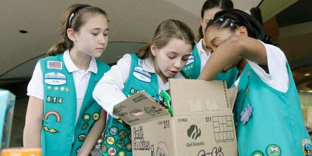 FILE -- Girl Scouts Caroline Jahr, 11, from left, Audrey Figari, 12, and Angelica Armstrong, 10, sort through a case of Girl Scout cookies, Friday, Feb. 23, 2007, in Dallas.