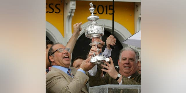 May 16, 2015: American Pharoah owner Ahmed Zayat, left, and Maryland Gov. Larry Hogan hold the Woodlawn Vase after American Pharoah with Victor Espinoza aboard won the 140th Preakness Stakes horse race at Pimlico Race Course in Baltimore. (AP Photo/Matt Slocum, File)