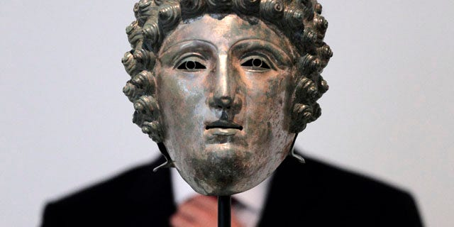 September 13: A Christie's employee poses for photographs behind a Roman bronze helmet found with the use of a metal detector, at the auction house's offices in London. The helmet is topped with a griffin. The face mask features perfectly arched eyebrows and an ancient gaze, framed by curls. And it is up for auction. (AP)