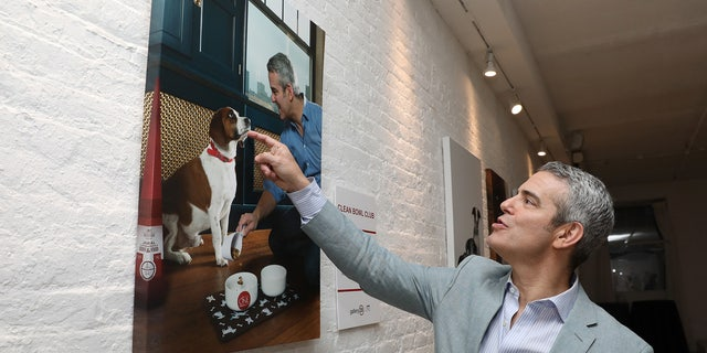 """Cohen says that he and """"RHOB"""" star Lisa Vanderpump share a love of dogs. Here, the TV hosts admires photos of himself and his dog Wacha at the Purina One gallery in New York City."""