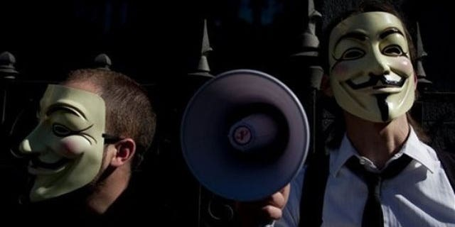 """In this May 15, 2011 file photo people wearing masks often used by a group that calls itself """"Anonymous"""" take part in a rally in Madrid."""