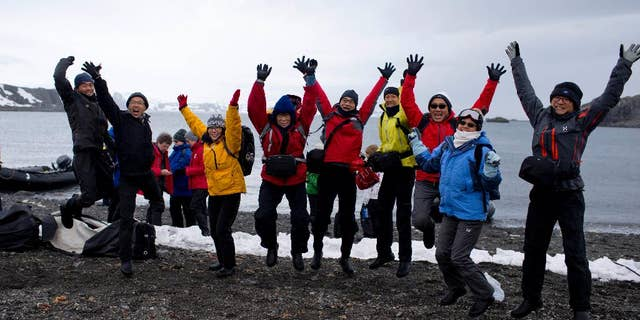 In this Feb. 2, 2015 photo, tourists jump as they pose for a picture, after disembarking from the Ocean Nova cruise ship, on King George Island, Antarctica. This tourist season, which runs November through March, more than 37,000 visitors are expected to walk on the coldest continent on Earth, about 10 percent more than the year before. (AP Photo/Natacha Pisarenko)