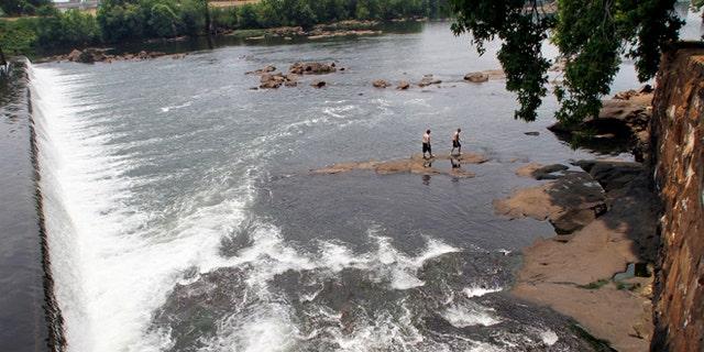 June 11, 2011: Men walk on the rocks in the Chattahoochee River below the City Mills dam near Columbus, Ga.