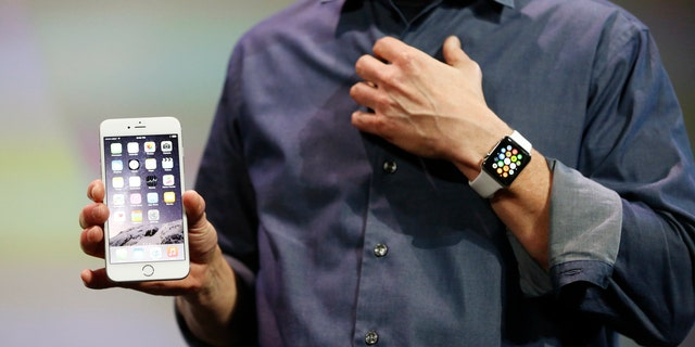 Apple CEO Tim Cook wears the Apple Watch and shows the iPhone 6 Plus during an Apple event at the Flint Center in Cupertino, California.
