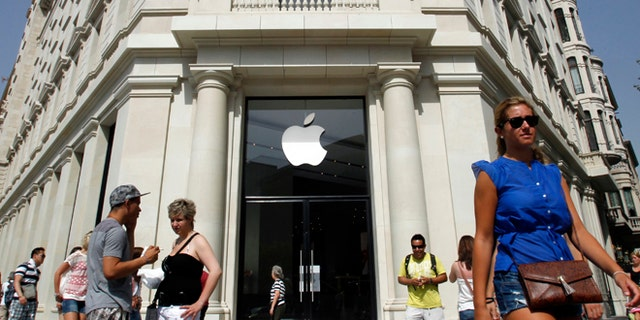July 26: People walk past a closed shop, which will be opened and inaugurated as the largest Apple store in southern Europe at Passeig de Gracia, in Barcelona.