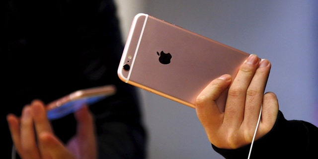 File photo - Customers hold the iPhone 6s during the official launch at the Apple store in central Sydney, Australia, Sept. 25, 2015.