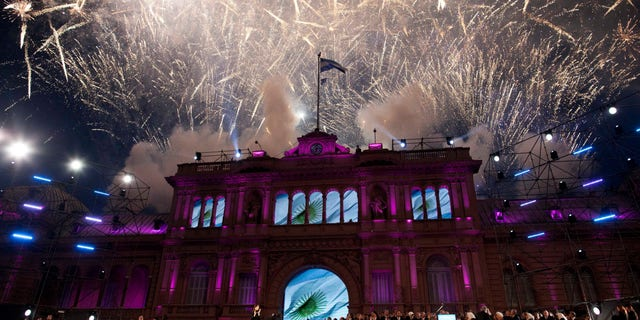 The government house is bathed in purple light as fireworks explode over a government rally in Buenos Aires, Argentina, Saturday, May 25, 2013. Cristina Fernandez's government and supporters are celebrating 10 years since she and her late husband Nestor Kirchner have held office, and the 203th anniversary of Argentina's May Revolution. (AP Photo/Natacha Pisarenko)