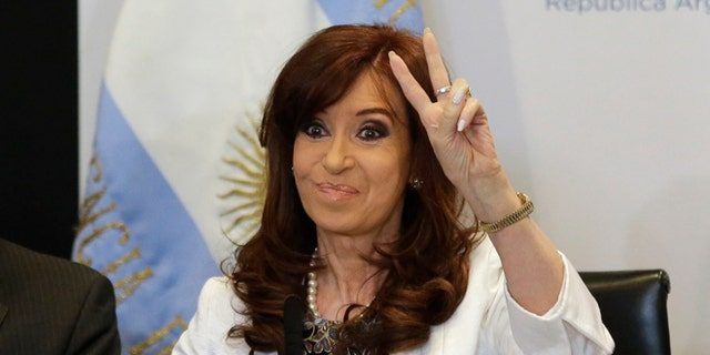 President Cristina Fernandez gestures to supporters during the presentation of a new 100-peso bill at Casa Rosada presidential palace in Buenos Aires, Argentina, Thursday, March 26, 2015. A federal appeals court on Thursday threw out a case that accused Fernandez and other top officials of a major cover up deal with Iran, giving a victory of sorts to an administration that has been rocked by the mysterious death of the prosecutor who made the allegations. (AP Photo/Victor R. Caivano)