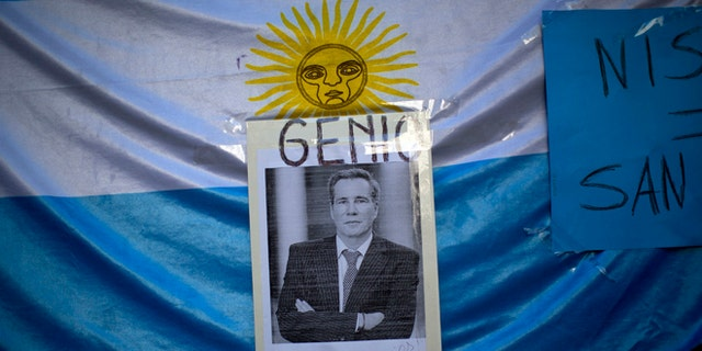 """A portrait of late prosecutor Alberto Nisman is seen pasted on an Argentine flag with a title that reads in Spanish """"Genius,"""" outside a funeral home during his wake in Buenos Aires, Argentina, Thursday, Jan. 29, 2015. Nisman was scheduled to appear before congress the day after he was found dead in his apartment on Jan. 18, to detail his allegations that President Cristina Fernandez had conspired to protect some of the Iranian suspects in the 1994 bombing of a Jewish center. The man who gave Nisman the gun that killed him said Wednesday that Nisman feared for the safety of his daughters and didn't trust the policemen protecting him. (AP Photo/Rodrigo Abd)"""