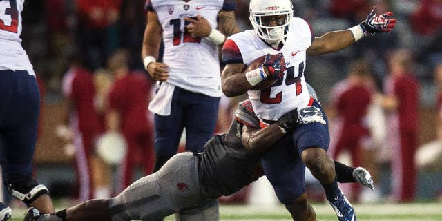 Arizona wide receiver Terris Jones-Grigsby (24) is tackled by Washington State linebacker Kache Palacio during the third quarter of an NCAA college football game Saturday, Oct. 25, 2014, in Pullman, Wash. Arizona won 59-37. (AP Photo/Dean Hare)