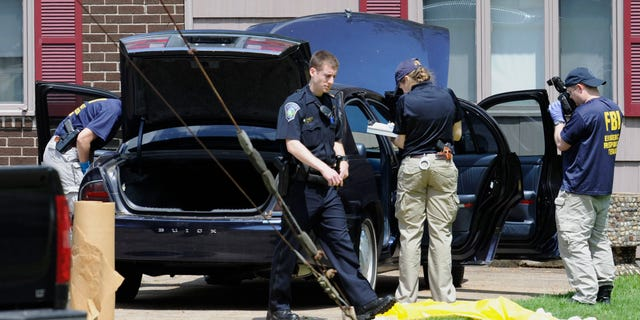 Law enforcement agents search a car at the home of reputed Connecticut mobster Robert Gentile in Manchester, Conn., Thursday, May 10, 2012. Gentile's lawyer A. Ryan McGuigan said at the time that the FBI warrant allowed the use of ground-penetrating radar and believes they were looking for paintings stolen from Boston's Isabella Stewart Gardner Museum.