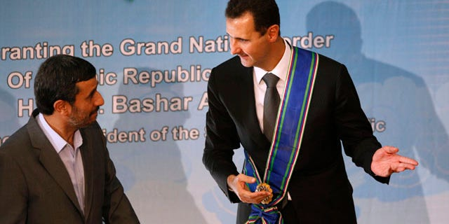Oct. 2: Syrian President Bashar Assad, right, gestures, after he is awarded with Iran's highest national medal by his Iranian counterpart Mahmoud Ahmadinejad, in Tehran, Iran. Assad has overlooked the White House's efforts to improve relations in favor of alliances with Iran and militant groups such as Hezbollah and the Palestinian Hamas.