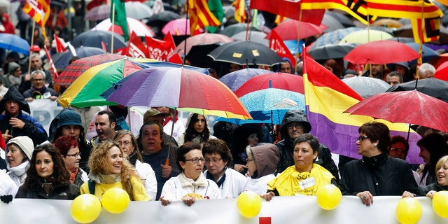 People hold umbrellas as they march with a banner during a protest against government austerity measures in Barcelona.