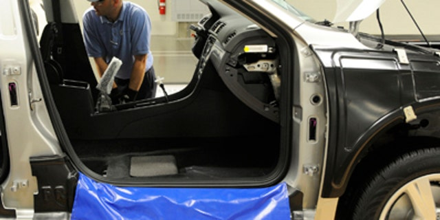 In this June 28, 2011 photo, Ben Edwards, team leader on assembly line number 6, makes adjustments to the door frame of a new Volkswagen Passat in Chattanooga, Tennessee. Mr. Edwards is a new auto employee at the Volkswagen plant which opened on May 24, 2011. (AP Photo/Billy Weeks)