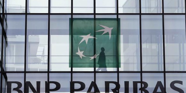 June 2, 2014: An employee walks behind the logo of BNP Paribas in the company's headquarters in Issy-les-Moulineaux, near Paris. (REUTERS/CHARLES PLATIAU)