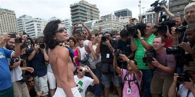 """A woman poses for photos during a protest against a topless ban on the Ipanema beach, in Rio de Janeiro, Brazil, Saturday, Dec. 21, 2013. A much-hyped protest for the right to go topless on Rio de Janeiro's beaches fell flat Saturday when only a handful of women bared their chests for the movement. Under Brazil's penal code, which dates back to the 1940s, female toplessness is an """"obscene act,"""" punishable by three months to a year in prison, or fines. (AP Photo/Silvia Izquierdo)"""