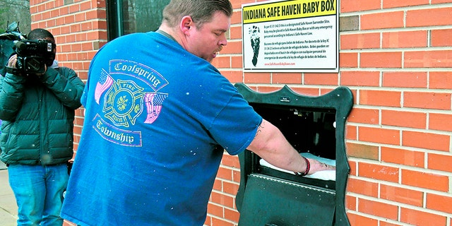 In this Monday, April 9, 2018, photo, Lt. Chuck Kohler, with the Coolspring Township Volunteer Fire Department, shows how a mother can relinquish her newborn, anonymously and without fear of prosecution, using the Safe Haven Baby Box, in Michigan City, Ind.