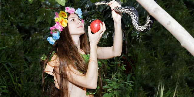 Young girl with floral wreath on her head holding an apple in one hand and a snake in the other. Foliage forest on dark background. Temptation of Eve.
