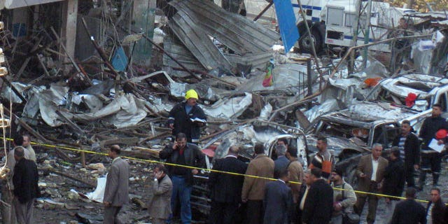 December 22, 2011: Iraqi security forces and people inspect the scene of a car bomb attack in Baghdad. A series of blasts Thursday morning in Baghdad killed and wounded scores of people in a coordinated attack designed to wreak havoc across the Iraqi capital.