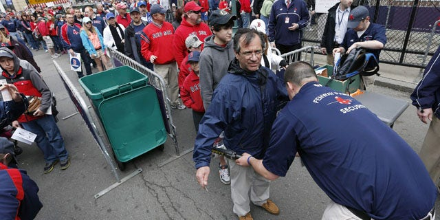 FILE - In this April 20, 2013 file photo, fans pass through security before entering Fenway Park for a baseball game between the Boston Red Sox and the Kansas City Royals in Boston. Major League Baseball has told its 30 teams they must implement security screening for fans by 2015. (AP Photo/Michael Dwyer, File)