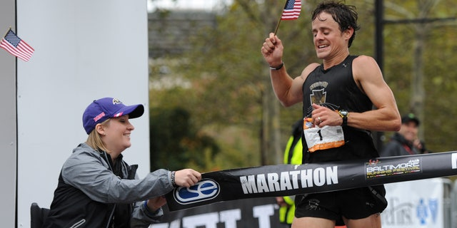 Oct. 12, 2013: Boston marathon bombing survivor Erika Brannock holds an end of the tape at the finish line as runner David Berden wins the Baltimore marathon.