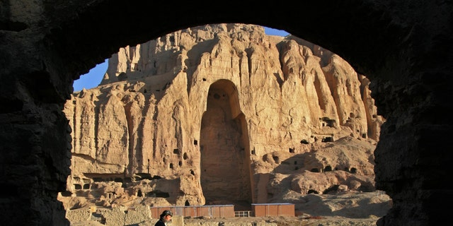 An Afghan man rides his motorcycle past the remains of the Giant Buddha destroyed by the Taliban in March 2001 in central Bamiyan province 162 miles northwest of Kabul March 30, 2005.