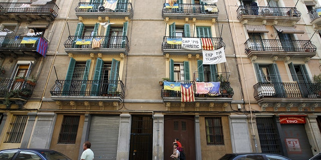 """Banners against touristic apartments hang from balconies as people walk past them at Barceloneta neighborhood in Barcelona, Spain. The banner reads """"no touristic apartments."""""""