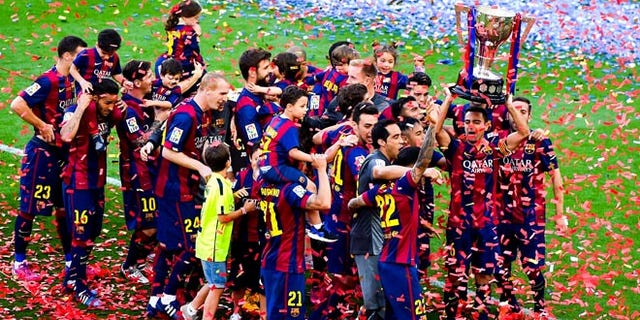 FC Barcelona players celebrate with La Liga trophy at Camp Nou on May 23, 2015 in Barcelona, Spain.
