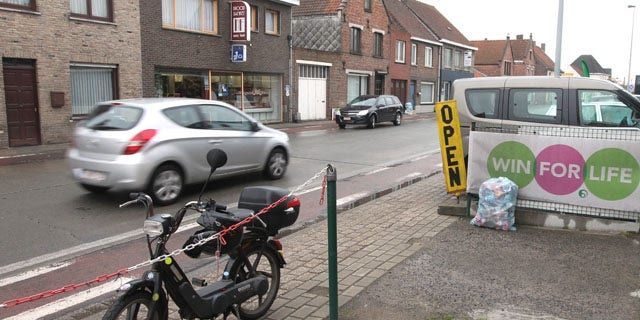 May 2, 2013: A car passes along where robbers lost their cool and threw the vault they had stolen nearby out the car right onto the street causing a 'rainstorm of money', in Zedelgem, western Belgium.