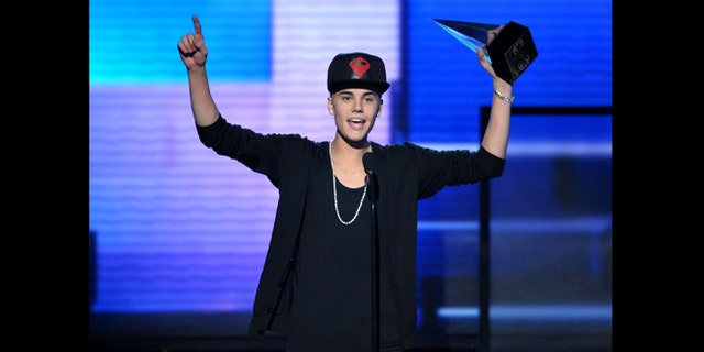 """Nov. 18, 2012: File photo, Justin Bieber accepts the award for favorite album - pop/rock for """"Believe"""" at the 40th Anniversary American Music Awards, in Los Angeles. A Los Angeles appellate panel wrote in a preliminary statement filed Monday, Jan. 28, 2013, that a 2010 California anti-paparazzi statute is constitutional. The law was used to charge a photographer for chasing Bieber last year, but a judge dismissed the anti-paparazzi counts in November 2012 because he said the law is overly broad and unconstitutional."""