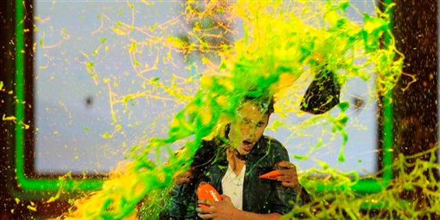 Justin Bieber gets slimed after accepting the award for favorite male singer onstage at Nickelodeon's 25th Annual Kids' Choice Awards.