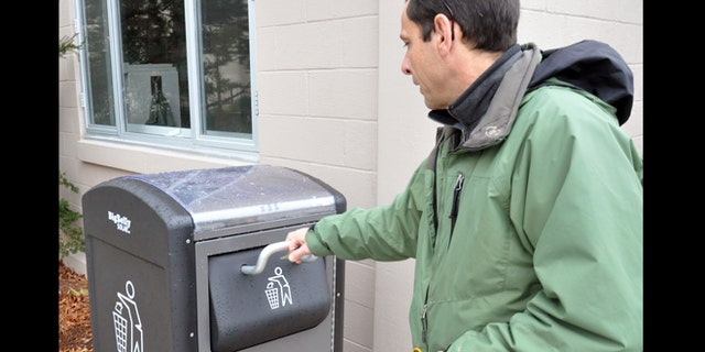 Dec. 5, 2012: Rich Valcourt checks on a BigBelly solar-powered waste disposal unit at Natick Soldier Systems Center, Mass. NSSC has 12 of the units positioned across the installation.