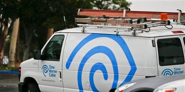 A Time Warner Cable service truck works its way through traffic May 27, 2015, in Carlsbad, Calif.