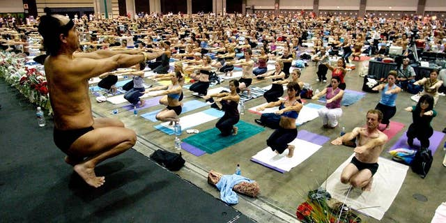 FILE - This Sept. 27, 2003 file photo Bikram Choudhury, front, founder of the Yoga College of India and creator and producer of Yoga Expo 2003, leads a yoga class at the Expo at the Los Angeles Convention Center. A half-dozen women claim Choudhury, the founder of the popular hot yoga studios that bear his name groped, harassed or sexually assaulted them. The most recent case filed this month claims that Choudhury raped a former student in 2010. (AP Photo/Reed Saxon,File)