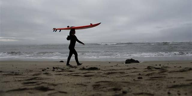 This file photo shows a surfer carrying her surfboard in Half Moon Bay, Calif.
