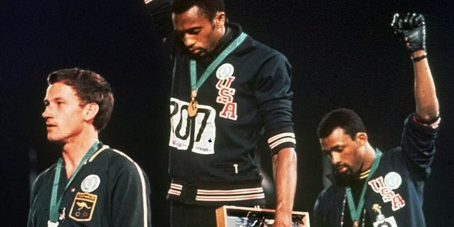 """In this file photo, United States gold medalist Tommie Smith, center, and bronze medalist John Carlos, right, stare downward while extending their gloved hands skyward in racial protest alongside Australian silver medalist Peter Norman during the playing of """"The Star-Spangled Banner"""" following the 200-meter race at the Mexico City Summer Olympics.(AP)"""