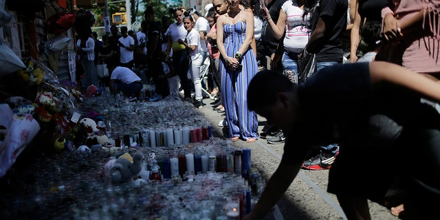 People leave candles and other mementos at a memorial to Lesandro Guzman-Feliz near the site of his murder in the Bronx five days after the June 20 murder.