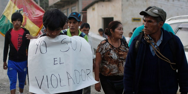 """In this June 6, 2015 photo, a man is made to wear a sign with a handwritten message that reads in Spanish; """"I'm the rapist,"""" as he is paraded through La Asunta, northeast of La Paz, Bolivia. Groups of citizens patrol the town of 7,000 people, who have imposed a sort of vigilante dry law in the coca-growing mountain town,  hoping to end a series of rapes and other crimes. In recent months an 11-year-old girl, and 12-year old girl have been victims of rape in La Asunta, according to local officials. (AP Photo/Juan Karita)"""