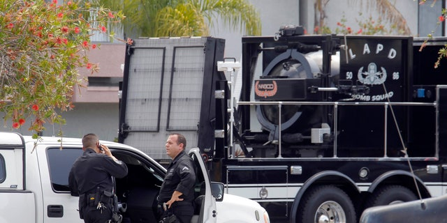 May 15, 2013: Los Angeles Police Department bomb squad officers gather at the site where police arrested a man after discovering explosive material in his car and potential explosive devices in his apartment.