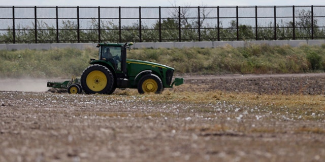 In this Sept. 6, 2012, photo, a tractor is used to farm in cotton field along a border fence that passes through the property  in Brownsville, Texas. Since 2008, hundreds of landowners on the U.S.-Mexico border have sought fair prices for property that was condemned to make way for the fence, but many of them received initial offers that were far below market value. (AP Photo/Eric Gay)