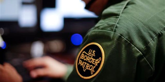 A Border Patrol agent uses a headset and computer to conduct a long-distance interview by video with a person arrested crossing the border in Texas.